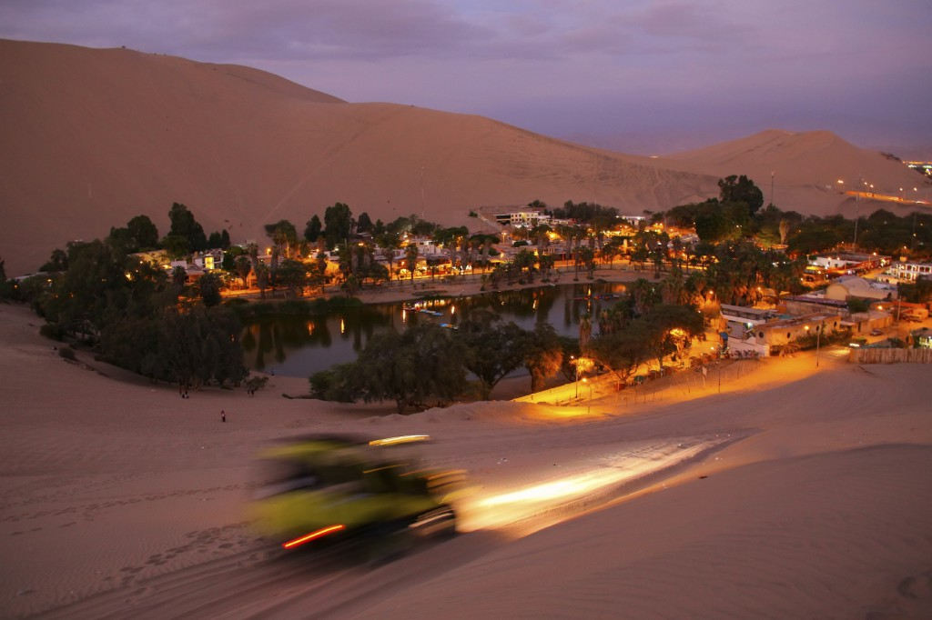 Oasis of  Huacachina at night with dune buggy blurred motion, Ica region, Peru.