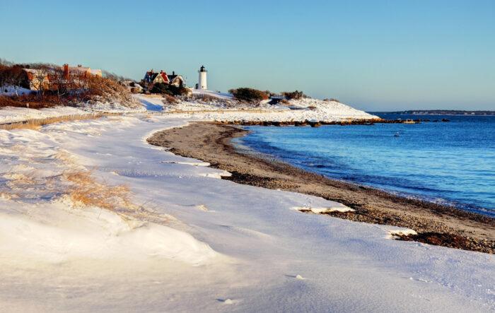 Coverd de neve, dunas e o farol em Cape Cod